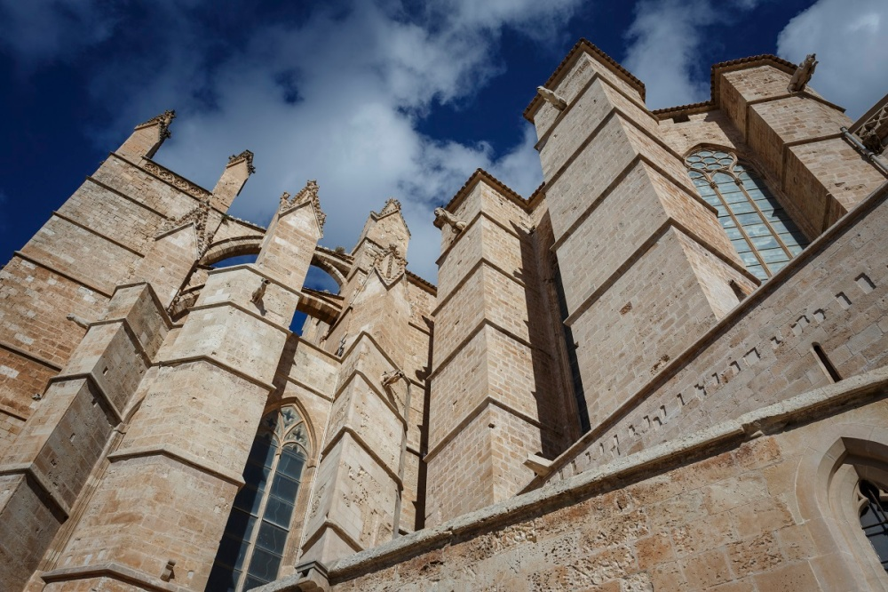 You see a part of the cathedral in Palma de Mallorca in front of the blue sky.