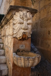 A really nice but unremarkable fountain at the edge of a staircase.
